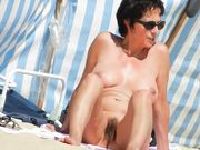 Mature nudist woman with nice hairy pussy at the beach